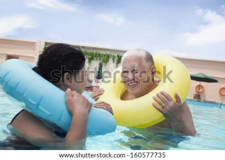 Senior couple smiling and relaxing in pool with inflatable tubes - stock photo
