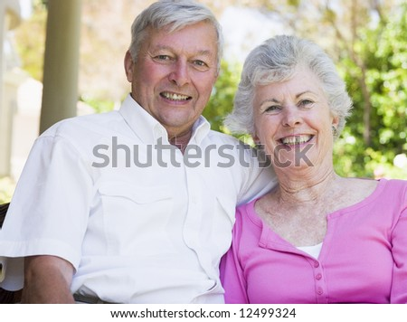 Senior couple smiling at camera sitting on garden seat - stock photo