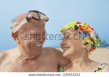 Senior couple smiling at each other at beach - stock photo