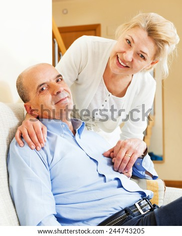 senior couple smiling  together on sofa in home interior