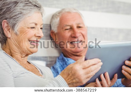 Senior couple smiling while using digital tablet in bedroom - stock photo
