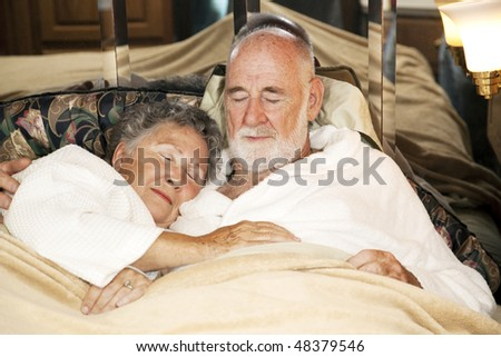 Senior couple sound asleep in the bed of their motor home. - stock photo