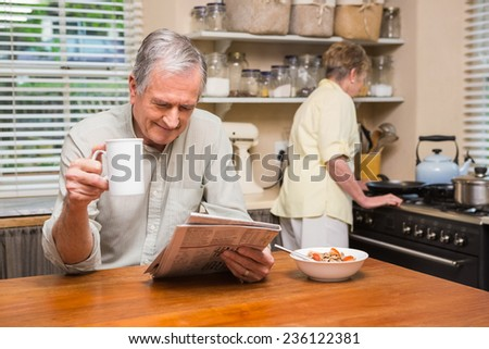 Senior couple spending the morning together at home in the kitchen - stock photo