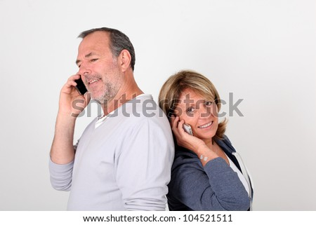 Senior couple standing back to back and using mobile phone