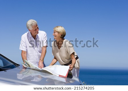Senior couple standing beside bonnet of parked car on clifftop overlooking Atlantic Ocean, consulting map, smiling - stock photo
