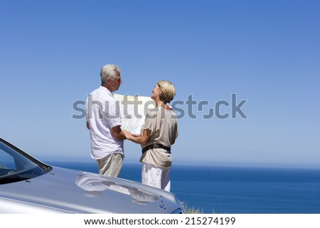 Senior couple standing beside parked car on clifftop overlooking Atlantic Ocean, consulting map, rear view - stock photo