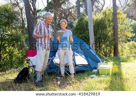 senior couple standing beside their tent - stock photo
