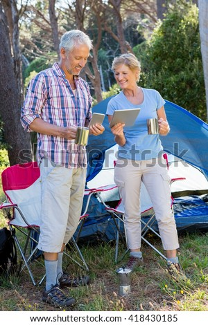 senior couple standing beside their tent in a forest - stock photo