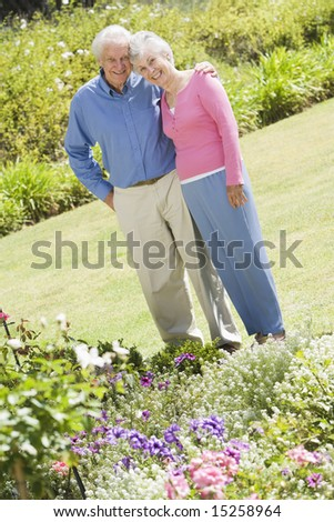 Senior couple standing in garden admiring flowerbed - stock photo