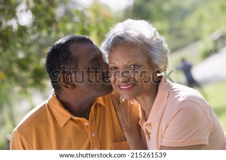 Senior couple standing in park, man kissing wife on cheek, smiling, close-up, portrait (tilt) - stock photo