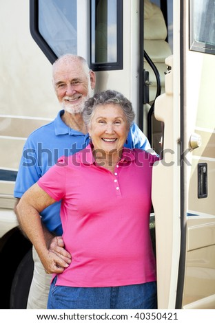Senior couple standing in the doorway of their luxury motor home. - stock photo