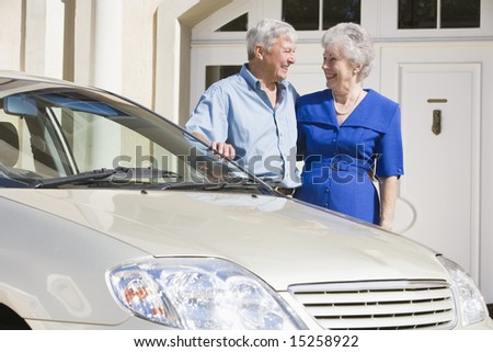 Senior couple standing next to car outside house - stock photo