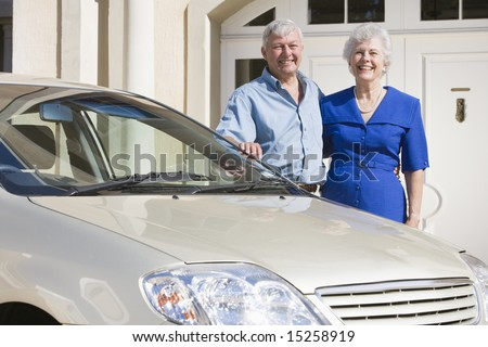 Senior couple standing next to new car outside house - stock photo