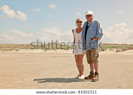 Senior couple standing on empty beach under clear blue sky on hot summer day. - stock photo