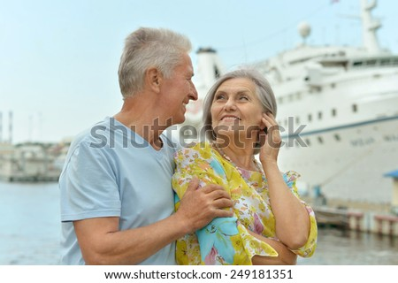 Senior couple standing on pier at the resort during vacation - stock photo