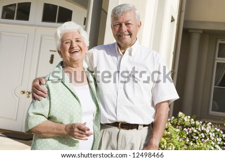 Senior couple standing outside front door of home - stock photo