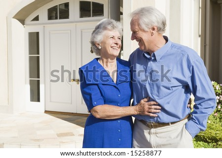 Senior couple standing outside front door of house - stock photo