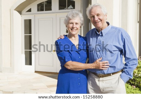Senior couple standing outside house - stock photo