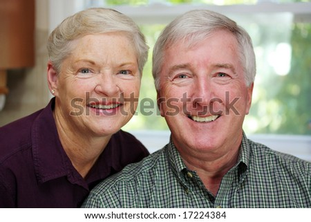 Senior Couple Standing Together In Their Home - stock photo