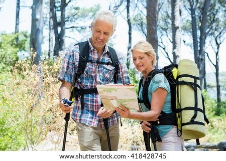 Senior couple standing with their stick and looking the map in a forest - stock photo