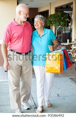 Senior couple strolling along with their shopping bags. - stock photo