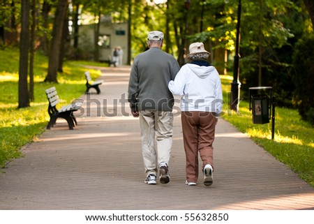 Senior couple strolling down a garden path together - stock photo