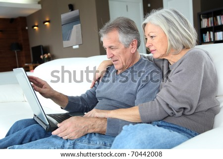 Senior couple surfing on internet at home - stock photo