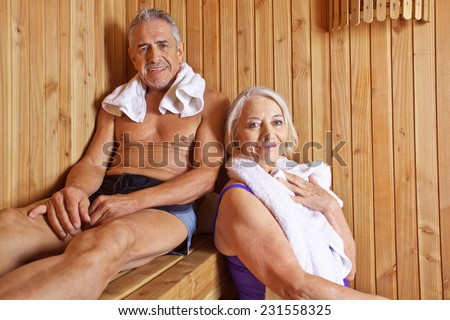 Senior couple sweating and smiling together in a hotel sauna - stock photo