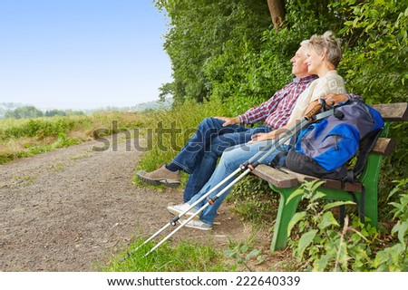 Senior couple taking a break on a bench while hiking in summer - stock photo