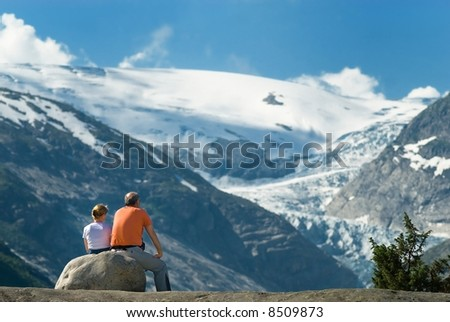 Senior couple taking a rest in front of a spectacular snow-capped mountain - stock photo