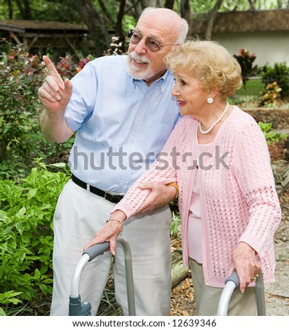 Senior couple taking a walk outdoors together.  She's using a walker. - stock photo