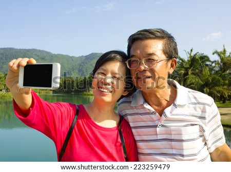 Senior couple taking picture by themselves outside with lake background - stock photo
