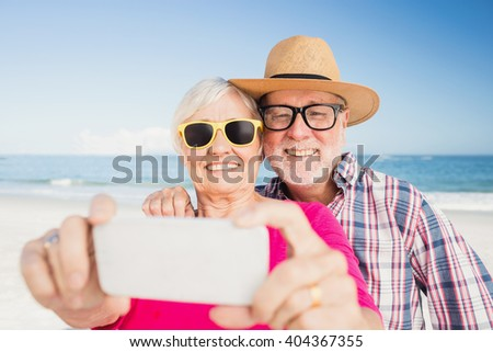 Senior couple taking selfie on the beach - stock photo