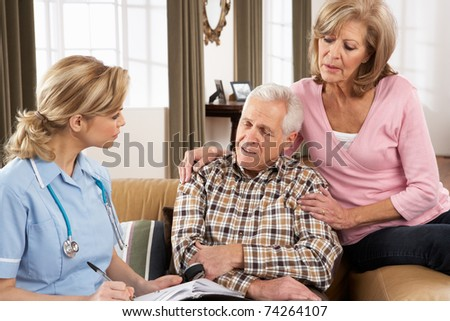 Senior Couple Talking To Health Visitor At Home - stock photo