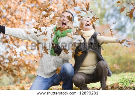 Senior couple throwing autumn leaves in the air - stock photo