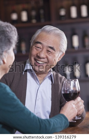 Senior Couple Toasting and Enjoying Themselves Drinking Wine, Focus on Male