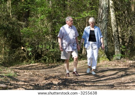 Senior couple together on a summerday strolling through the park - stock photo
