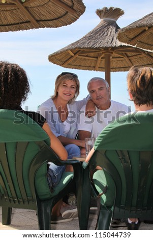 Senior couple under umbrellas - stock photo