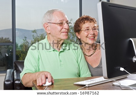 senior couple using a computer - stock photo