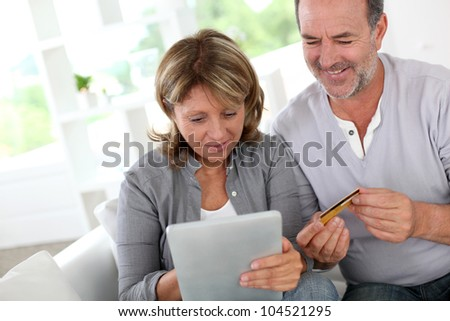 Senior couple using credit card to shop online - stock photo