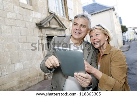 Senior couple using digital tablet in touristic area - stock photo
