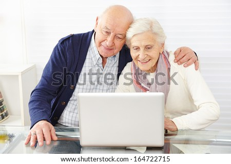 Senior couple using ecommerce in internet with laptop computer - stock photo