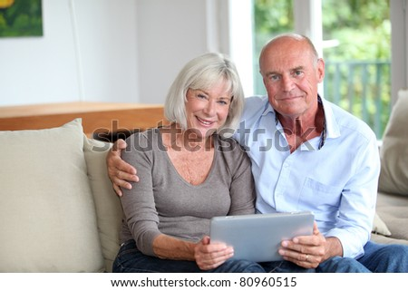 Senior couple using electronic tablet at home - stock photo