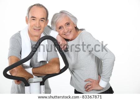 Senior couple using gym equipment - stock photo