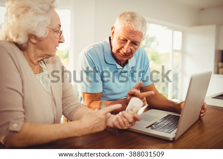 Senior couple using laptop and holding pills at home - stock photo