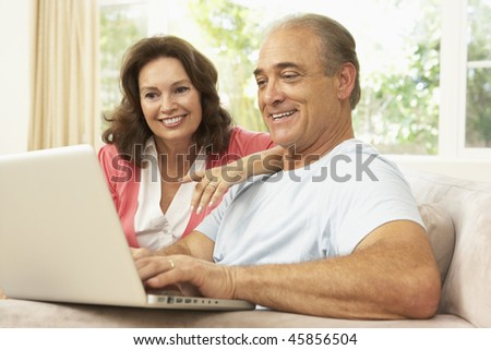 Senior Couple Using Laptop At Home - stock photo