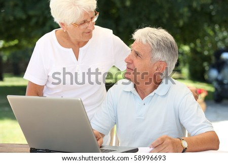 Senior couple using laptop computer at home - stock photo