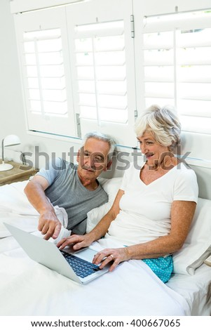 Senior couple using laptop on bed against window at home - stock photo