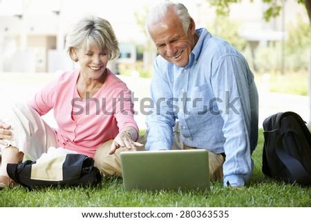 Senior couple using laptop outdoors - stock photo