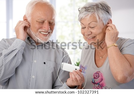 Senior couple using mp3, listening to music, smiling. - stock photo